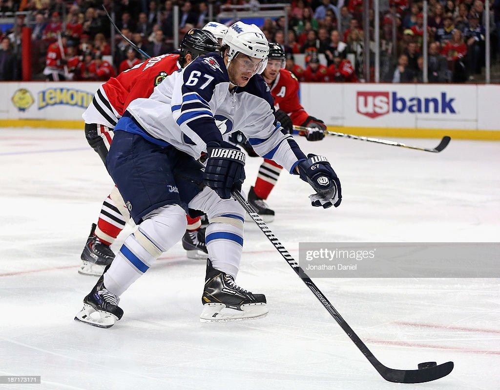 Michael Frolik #67 of the Winnipeg Jets skates past Brent Seabrook #7 of the Chicago Blackhawks at the United Center on November 6, 2013 in Chicago, Illinois.