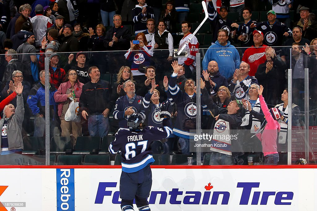 Michael Frolik #67 of the Winnipeg Jets throws his stick to fans in the stands after receiving second star honors following a 4-2 victory over the Detroit Red Wings at the MTS Centre on November 4, 2013 in Winnipeg, Manitoba, Canada.