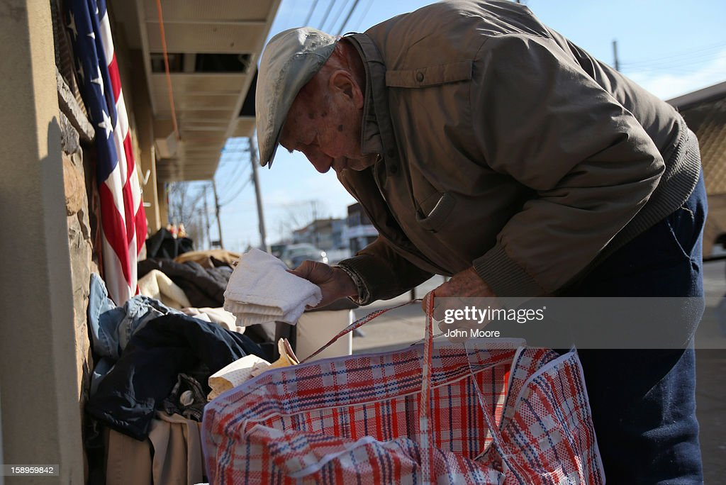 Michael Garo takes a set of towels from a Superstorm Sandy aid distribution center on January 4, 2013 in the Midland Beach area of the Staten Island borough of New York City. More than two months after the storm, Congress passed legislation today that will provide $9.7 billion to cover insurance claims filed by people whose homes were damaged or destroyed by Sandy.