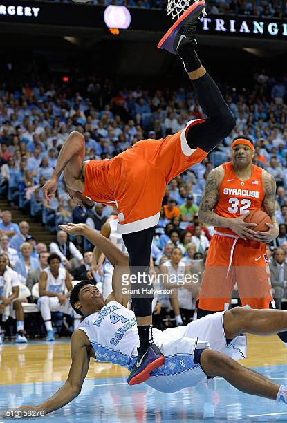 Michael Gbinije of the Syracuse Orange collides with Isaiah Hicks of the North Carolina Tar Heels during their game at the Dean Smith Center on...