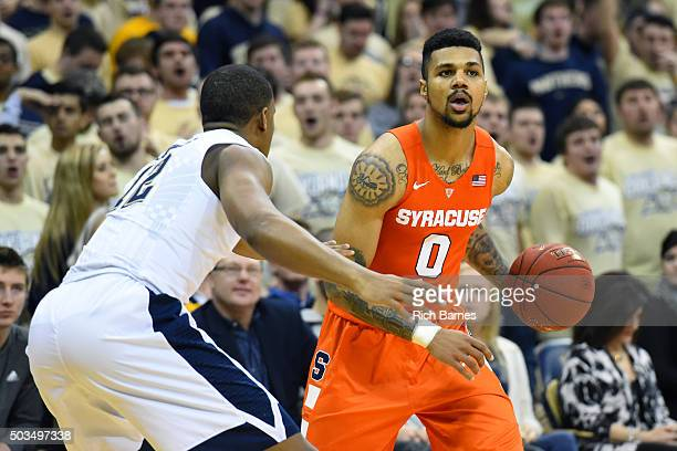 Michael Gbinije of the Syracuse Orange controls the ball against the defense of Chris Jones of the Pittsburgh Panthers during the second half at the...