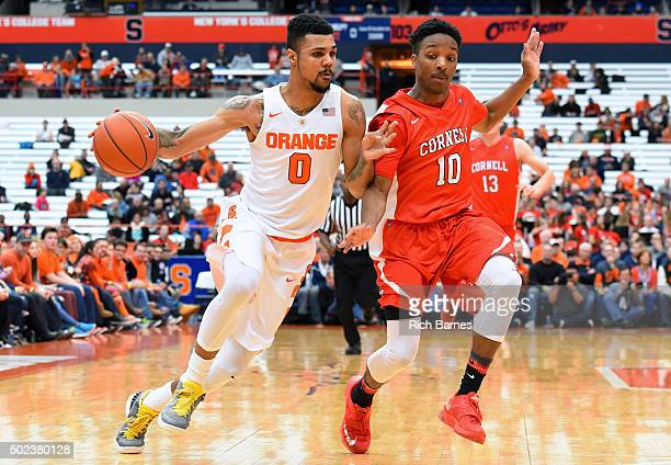 Michael Gbinije of the Syracuse Orange dribbles the ball up the court as Matt Morgan of the Cornell Big Red defends during the first half at the...