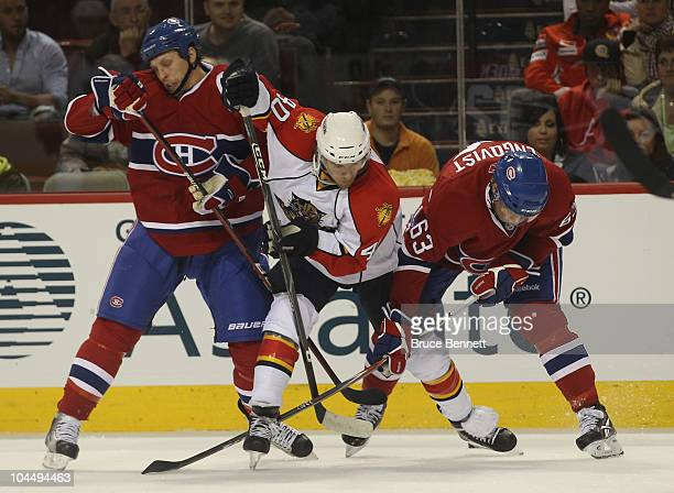 Michael Grabner of the Florida Panthers is checked by Travis Moen and Andreas Engqvist of the Montreal Canadiens at the Bell Centre on September 27...