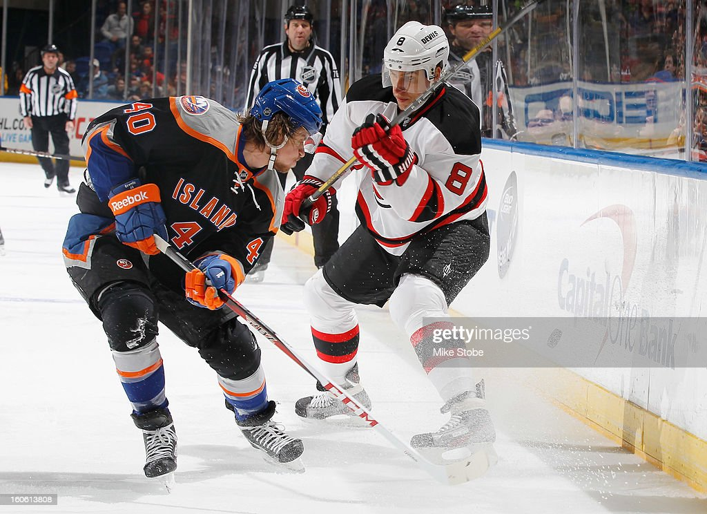 Michael Grabner #40 of the New York Islanders and Dainius Zubrus #8 of the New Jersey Devils battle for a loose puck at Nassau Veterans Memorial Coliseum on February 3, 2013 in Uniondale, New York. The Devils defeated the Islanders 3-0.