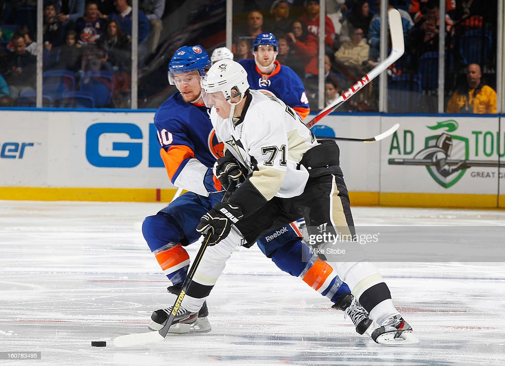 Michael Grabner #40 of the New York Islanders and Evgeni Malkin #71 of the Pittsburgh Penguins battle for the puck at Nassau Veterans Memorial Coliseum on Febuary 5, 2013 in Uniondale, New York.