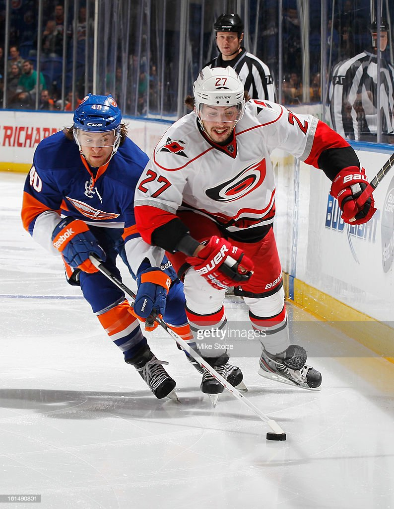 Michael Grabner #40 of the New York Islanders and Justin Faulk #27 of the Carolina Hurricanes pursue the puck at Nassau Veterans Memorial Coliseum on February 11, 2013 in Uniondale, New York.