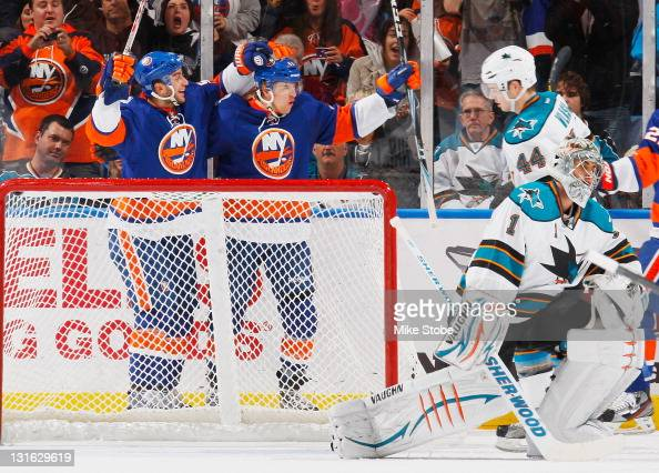 Michael Grabner of the New York Islanders celebrates a goal with teammate Frans Nielsen as Thomas Greiss of the San Jose Sharks looks on at Nassau...