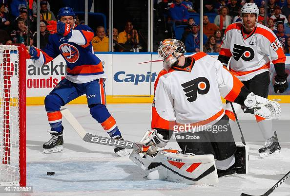 Michael Grabner of the New York Islanders celebrates as Rob Zepp of the Philadelphia Flyers reacts to a goal by Nikolay Kulemin of the New York...