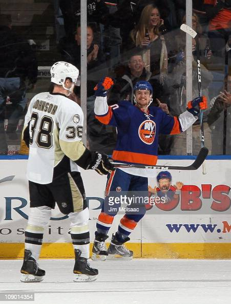 Michael Grabner of the New York Islanders celebrates his first period goal as Nick Johnson of the Pittsburgh Penguins skates away on February 11 2011...