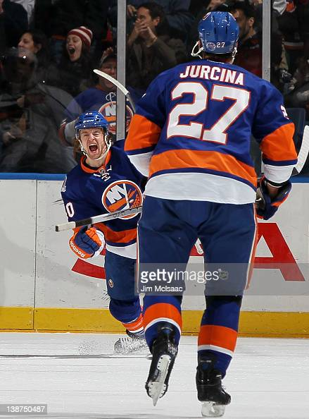Michael Grabner of the New York Islanders celebrates his first period goal against the Los Angeles Kings with teammate Milan Jurcina on February 11...