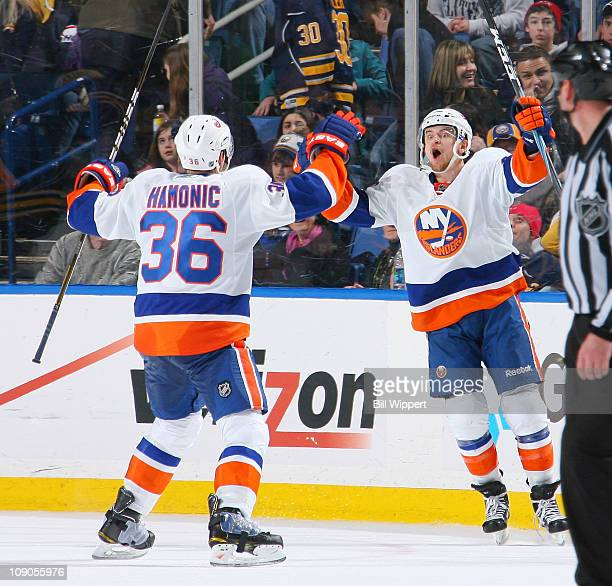 Michael Grabner of the New York Islanders celebrates his game winning overtime goal and third of the game with teammate Travis Hamonic against the...
