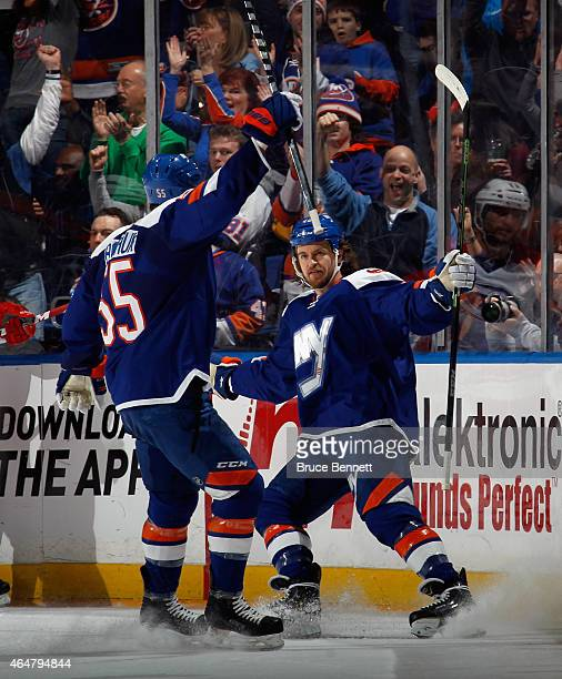 Michael Grabner of the New York Islanders celebrates his goal at 947 of the first period against the Carolina Hurricanes along with Johnny Boychuk at...