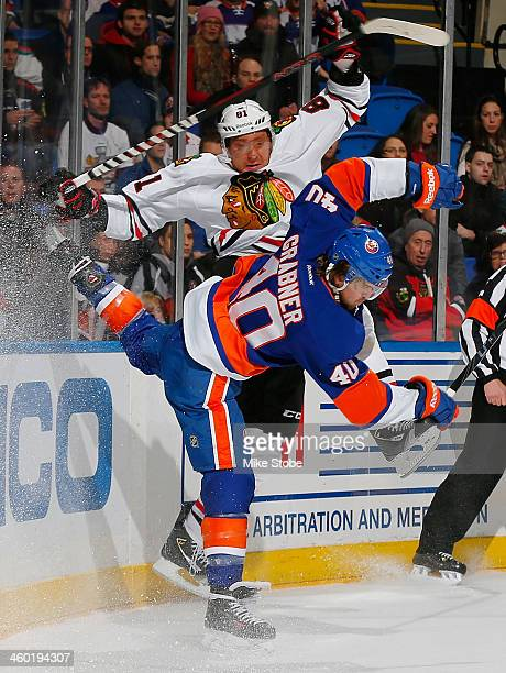 Michael Grabner of the New York Islanders collides with Marian Hossa of the Chicago Blackhawks at Nassau Veterans Memorial Coliseum on January 2 2014...