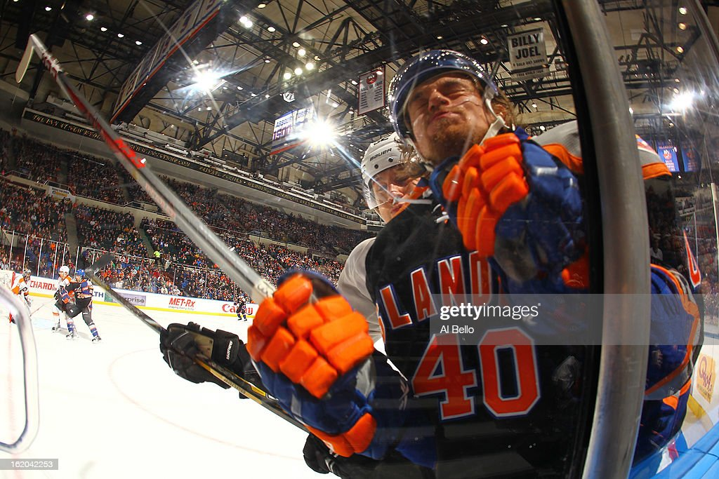 Michael Grabner #40 of the New York Islanders is checked by Tom Sestito #32 of the Philadelphia Flyers during their game at Nassau Veterans Memorial Coliseum on February 18, 2013 in Uniondale, New York.