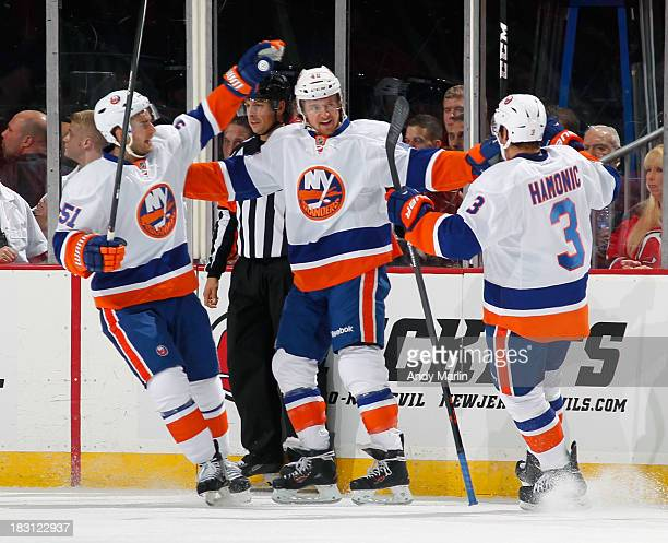 Michael Grabner of the New York Islanders is congratulated by his teammates after scoring a firstperiod goal against the New Jersey Devils during the...