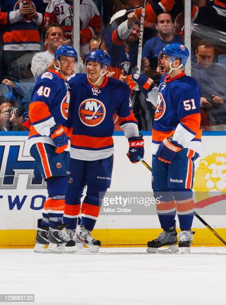 Michael Grabner of the New York Islanders is congratulated by teammates Kyle Okposo and Frans Nielsen on his second period goal in the game against...
