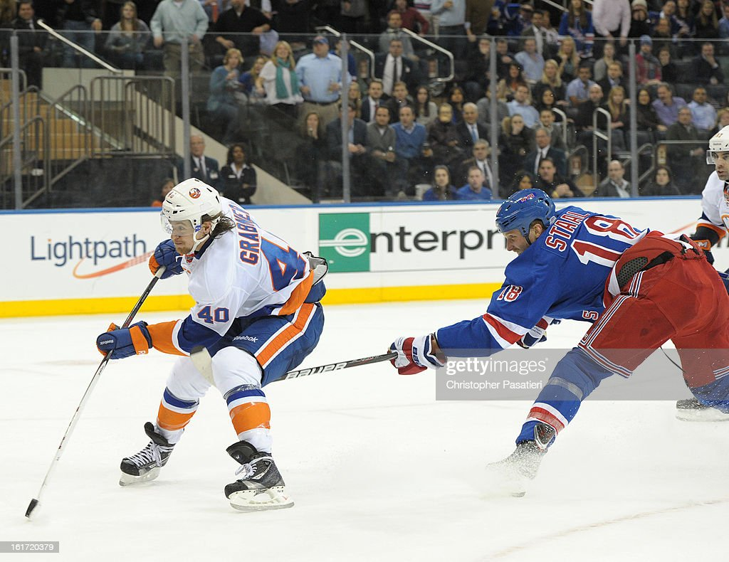 <a gi-track='captionPersonalityLinkClicked' href=/galleries/search?phrase=Michael+Grabner&family=editorial&specificpeople=537955 ng-click='$event.stopPropagation()'>Michael Grabner</a> #40 of the New York Islanders is hooked from behind by <a gi-track='captionPersonalityLinkClicked' href=/galleries/search?phrase=Marc+Staal&family=editorial&specificpeople=3809026 ng-click='$event.stopPropagation()'>Marc Staal</a> #18 of the New York Rangers as he skates in on a break-a-way in the overtime on February 14, 2013 at Madison Square Garden in New York City.