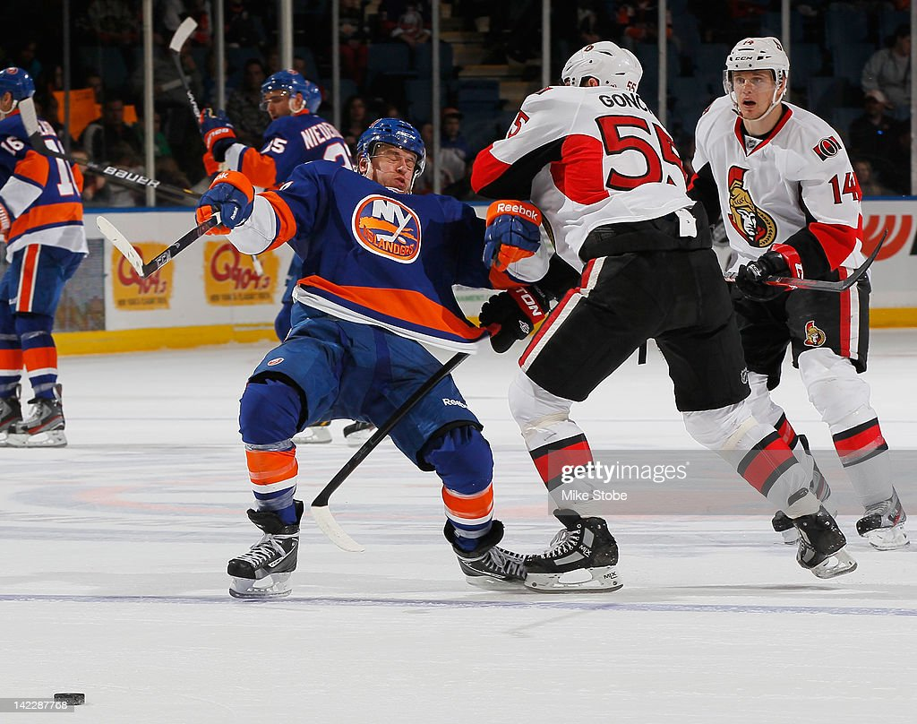 <a gi-track='captionPersonalityLinkClicked' href=/galleries/search?phrase=Michael+Grabner&family=editorial&specificpeople=537955 ng-click='$event.stopPropagation()'>Michael Grabner</a> #40 of the New York Islanders is knocked to the ice by <a gi-track='captionPersonalityLinkClicked' href=/galleries/search?phrase=Sergei+Gonchar&family=editorial&specificpeople=202470 ng-click='$event.stopPropagation()'>Sergei Gonchar</a> #55 of the Ottawa Senators at Nassau Veterans Memorial Coliseum on April 1, 2012 in Uniondale, New York. The Senators defeated the Islanders 5-1.