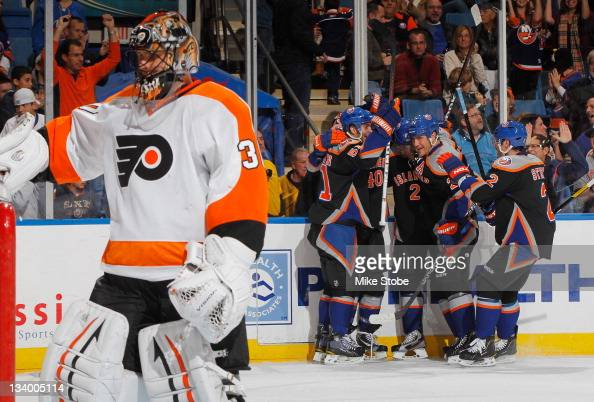 Michael Grabner of the New York Islanders is mobbed by teammates celebrating his first period goal as Ilya Bryzgalov of the Philadelphia Flyers looks...