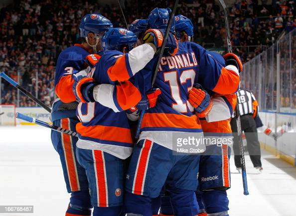 Michael Grabner of the New York Islanders is mobbed by teammates celebrating his first period goal during the game against the Florida Panthers at...