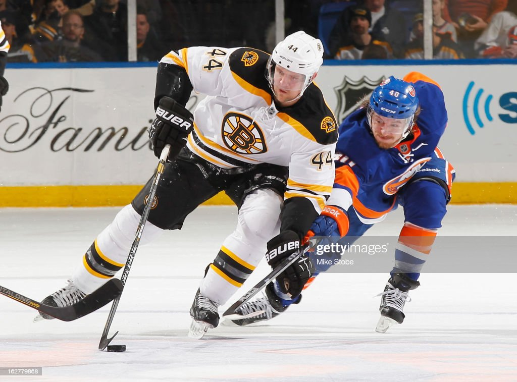 Michael Grabner #40 of the New York Islanders lunges to steal the puck from Dennis Seidenberg #44 of the Boston Bruins at Nassau Veterans Memorial Coliseum on February 26, 2013 in Uniondale, New York.