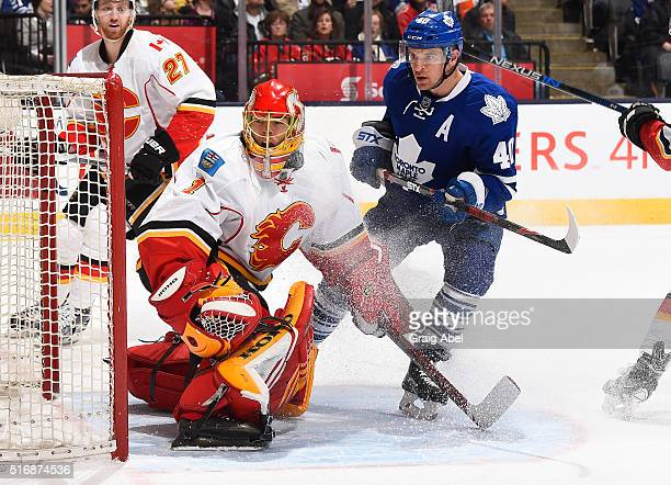 Michael Grabner of the Toronto Maple Leafs skates in front of Jonas Hiller of the Calgary Flames during game action on March 21 2016 at Air Canada...