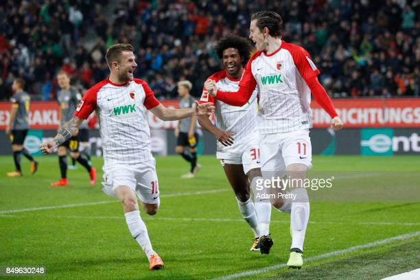 Michael Gregoritsch of Augsburg celebrates after he scored his teams first goal to make it 10 with Caiuby of Augsburg and Daniel Baier of Augsburg...