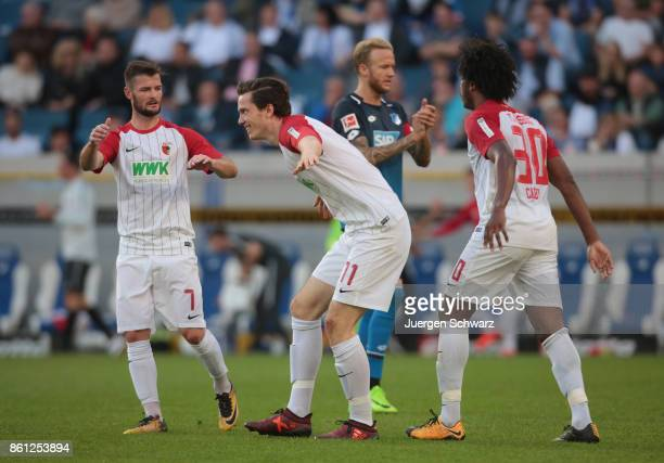 Michael Gregoritsch of Augsburg celebrates after scoring with Marcel Heller of Augsburg and Caiuby during the Bundesliga match between TSG 1899...