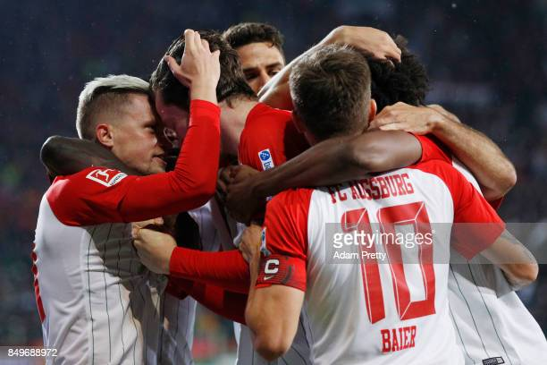 Michael Gregoritsch of Augsburg celebrates with team mates after he scored his teams first goal to make it 10 during the Bundesliga match between FC...