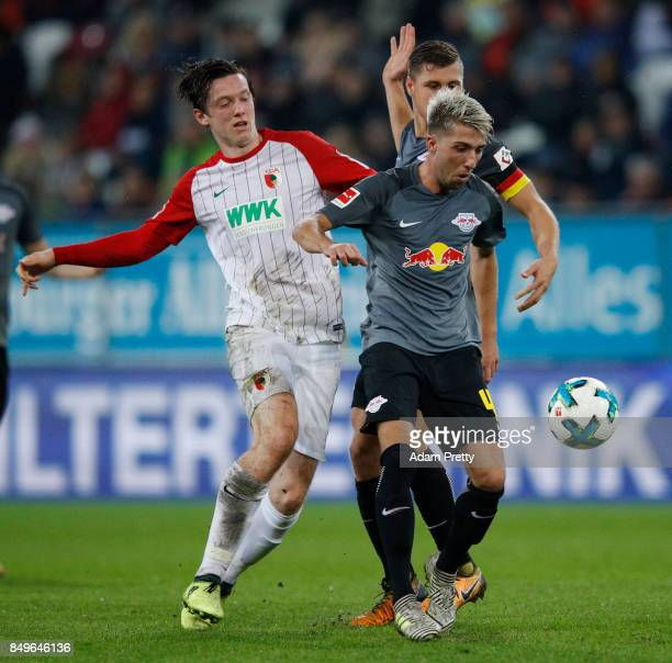 Michael Gregoritsch of Augsburg challenges Kevin Kampl of Leipzig during the Bundesliga match between FC Augsburg and RB Leipzig at WWKArena on...