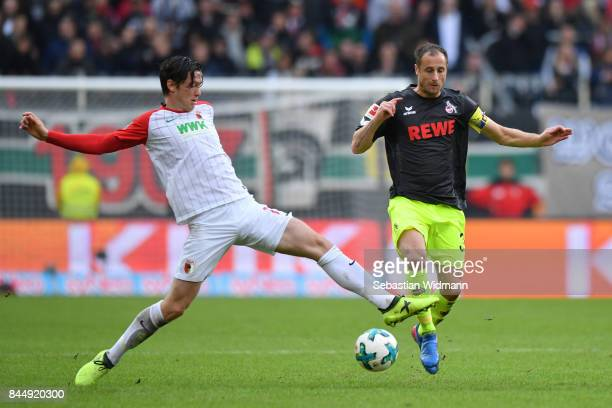 Michael Gregoritsch of Augsburg challenges Matthias Lehmann of Koeln during the Bundesliga match between FC Augsburg and 1 FC Koeln at WWKArena on...