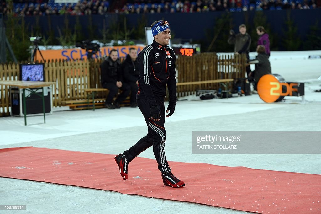 Michael Greis of Germany walks on a red carpet after the mixed mass start event at the World Team Challenge Biathlon in the German city of Gelsenkirchen on December 29, 2012. AFP PHOTO / PATRIK STOLLARZ