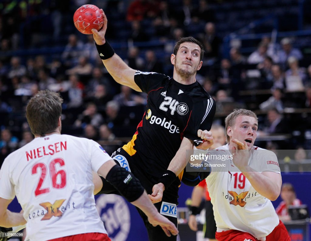 Michael Haas (C) of Germany shoots past Kasper Nilsen (L) and Rene Toft Hansen (R) of Denmarkduring the Men's European Handball Championship 2012 second round group one match between Denmark and Germany, at Arena Hall on January 23, 2012 in Belgrade, Serbia.