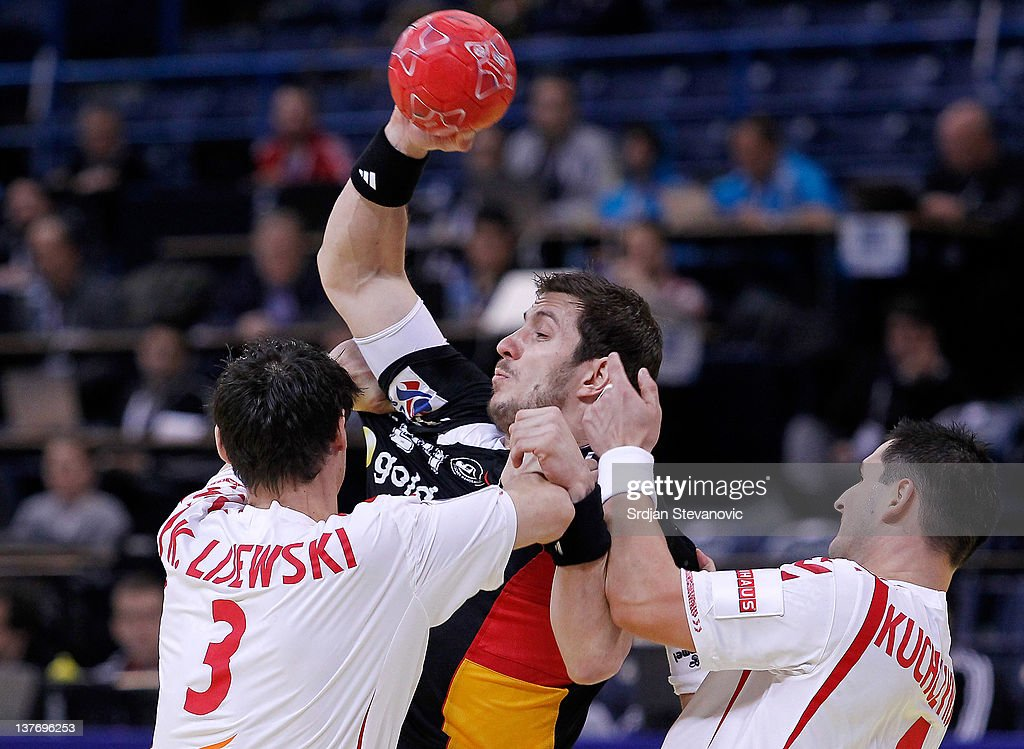 Michael Haas (L) of Germany vies with Patryk Kuchczynski (R) and Krzysztof Lijewski (L) of Poland during the Men's European Handball Championship 2012 second round group one match between Poland and Germany at Arena Hall on January 25, 2012 in Belgrade, Serbia.