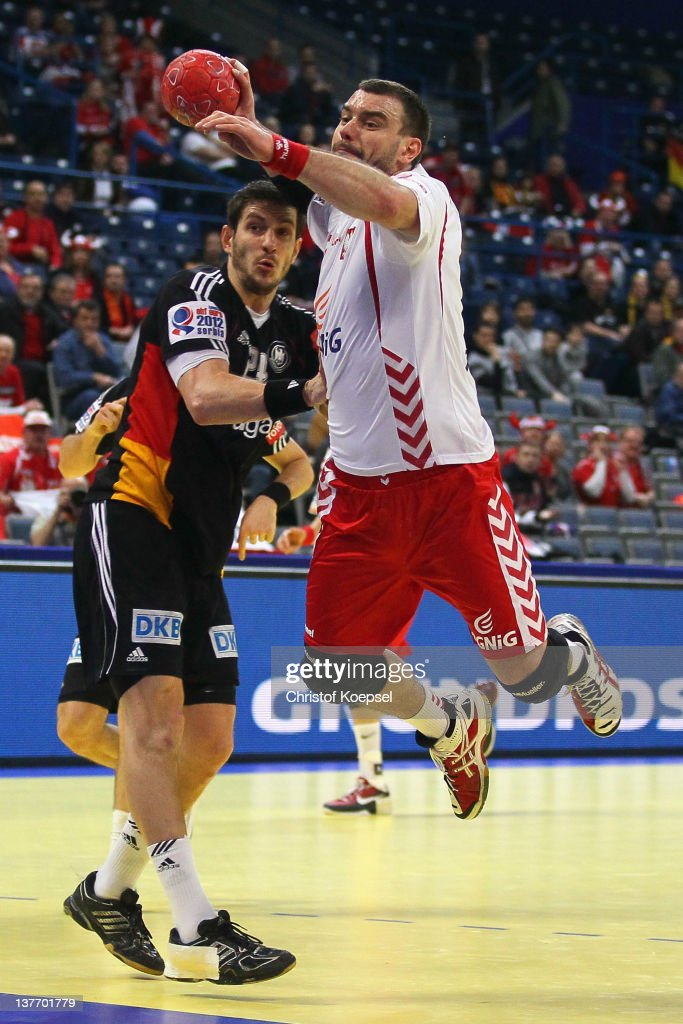 Michael Haass of Germany defends against Bartosz Jurecki of Poland during the Men's European Handball Championship second round group one match between Poland and Germany at Beogradska Arena on January 25, 2012 in Belgrade, Serbia.