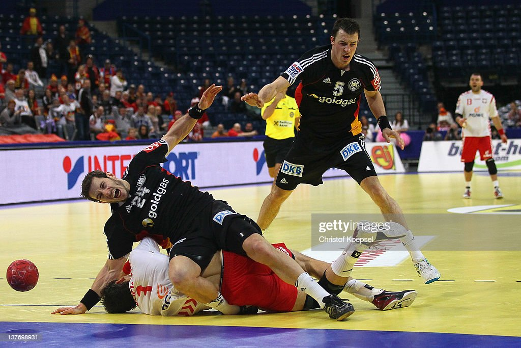 Michael Haass of Germany falls over Krzysztof Lijewski of Poland during the Men's European Handball Championship second round group one match between...