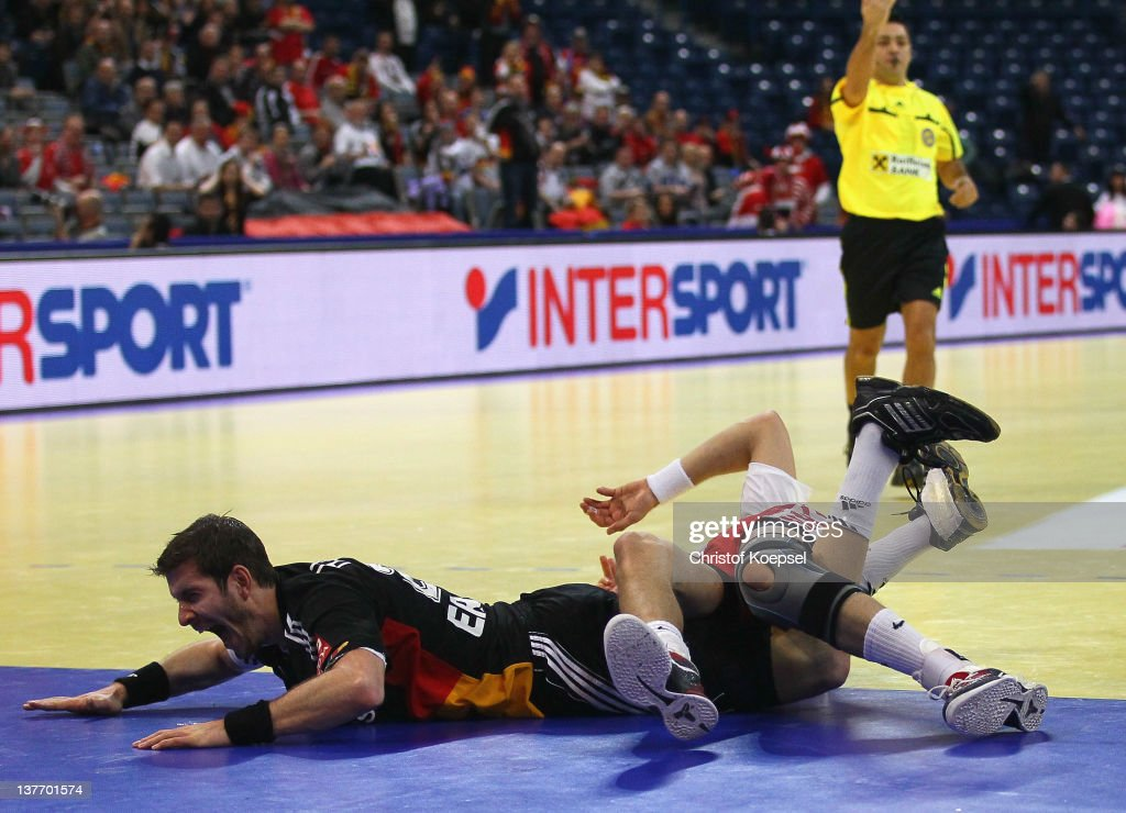 Michael Haass of Germany falls over Krzysztof Lijewski of Poland (R) during the Men's European Handball Championship second round group one match between Poland and Germany at Beogradska Arena on January 25, 2012 in Belgrade, Serbia.