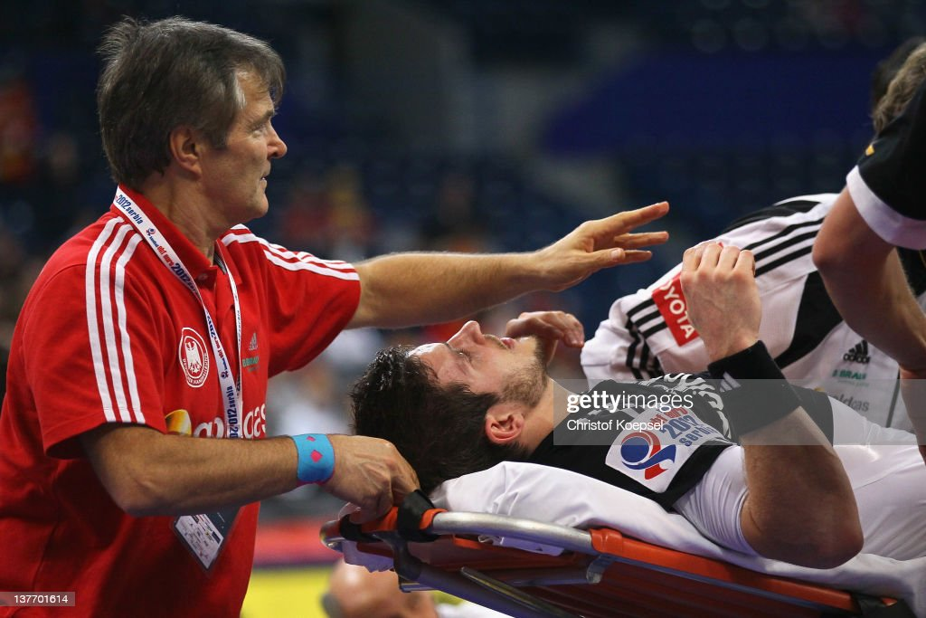 Michael Haass of Germany is treated after his injury during the Men's European Handball Championship second round group one match between Poland and Germany at Beogradska Arena on January 25, 2012 in Belgrade, Serbia.