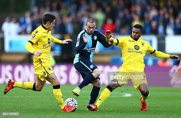 Michael Harriman of Wycombe Wanderers competes for the ball against Ashley Westwood and Leandro Bacuna of Aston Villa during the Emirates FA Cup...