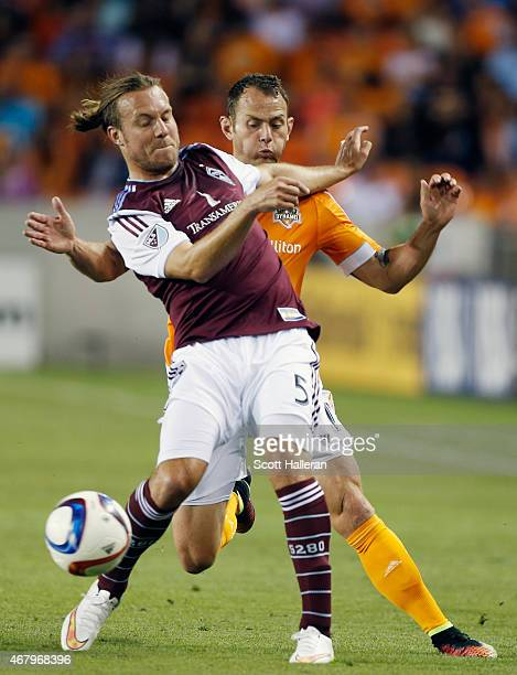 Michael Harrington of the Colorado Rapids battles for the ball with Brad Davis of the Houston Dynamo during their game at BBVA Compass Stadium on...