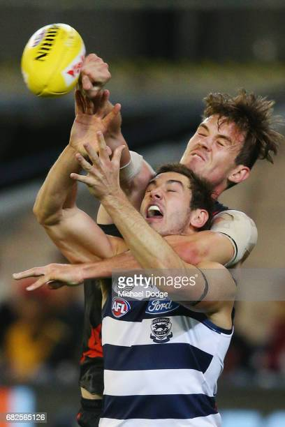 Michael Hartley of the Bombers punches the ball away from Daniel Menzel of the Cats during the round eight AFL match between the Essendon Bombers and...