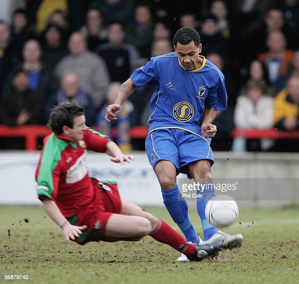 Michael Harvey of AFC Wimbledon gets tackled by David Warner of Windsor Eton during the Ryman League Premier Division match between AFC Wimbledon and...