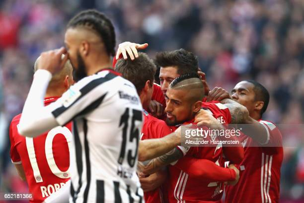 Michael Hector of Frankfurt reacts whilst Robert Lewandowski of Muenchen celebrates his 1st team goal with his team mates during the Bundesliga match...