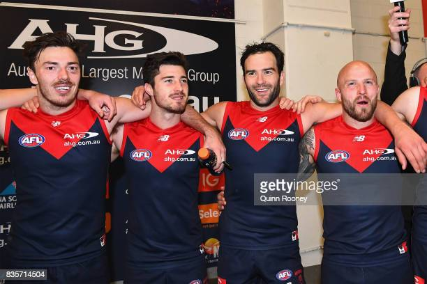 Michael Hibberd Alex NealBullen Jordan Lewis and Nathan Jones of the Demons sing the song in the rooms after winning the round 22 AFL match between...