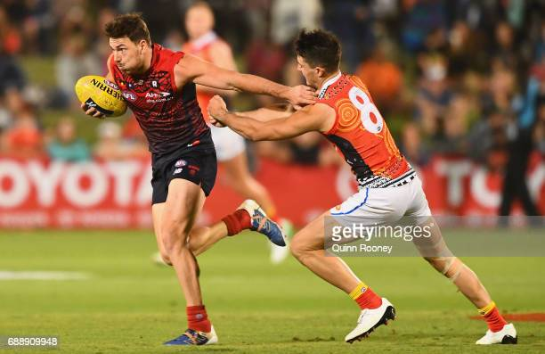 Michael Hibberd of the Demons fends off a tackle by Brayden Fiorini of the Suns during the round ten AFL match between the Melbourne Demons and the...