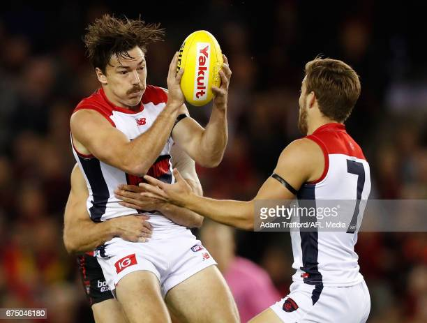 Michael Hibberd of the Demons is tackled by David Zaharakis of the Bombers during the 2017 AFL round 06 match between the Essendon Bombers and the...