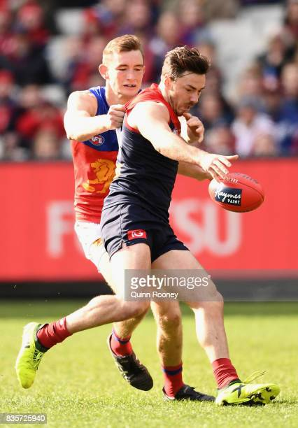 Michael Hibberd of the Demons kicks whilst being tackled by Harris Andrews of the Lions during the round 22 AFL match between the Melbourne Demons...