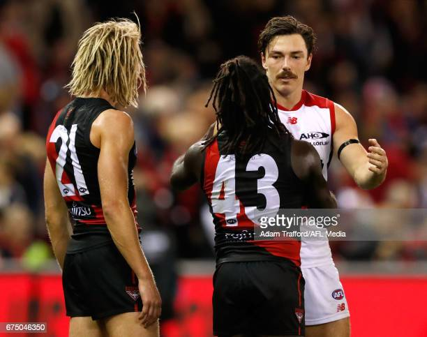 Michael Hibberd of the Demons shakes hands with former teammates Anthony McDonaldTipungwuti and Dyson Heppell of the Bombers during the 2017 AFL...