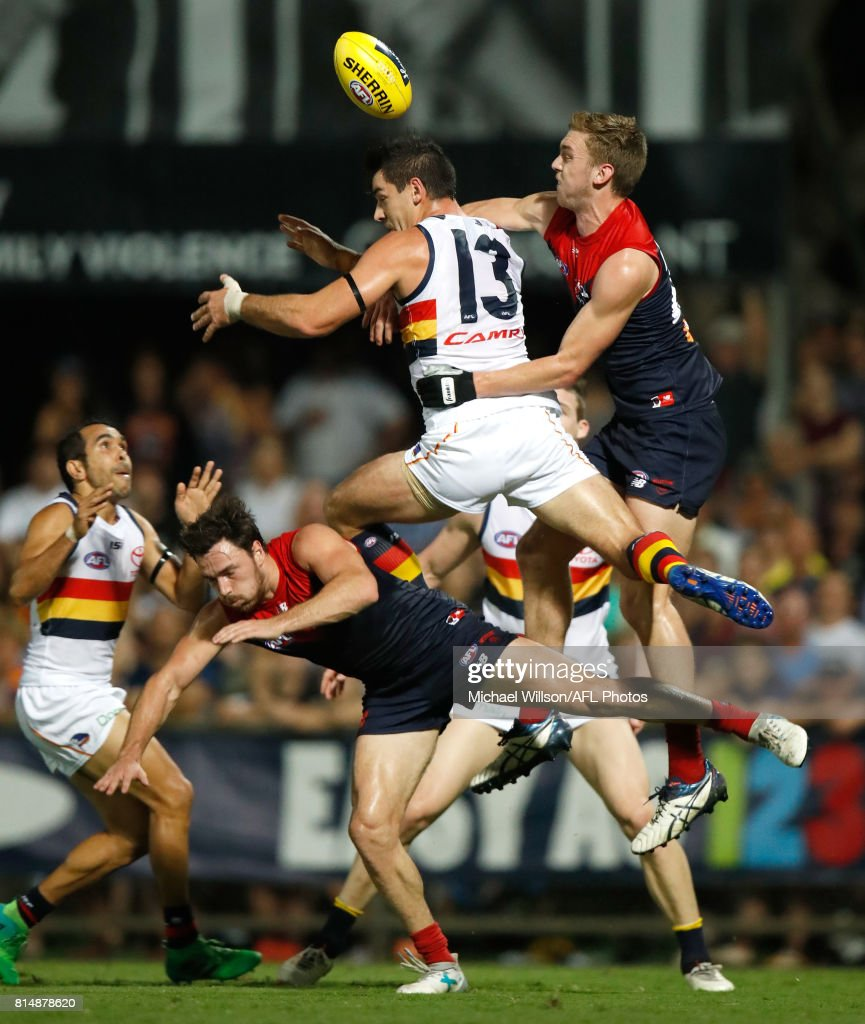Michael Hibberd of the Demons, Taylor Walker of the Crows and Oscar McDonald of the Demons compete for the ball during the 2017 AFL round 17 match between the Melbourne Demons and the Adelaide Crows at TIO Stadium on July 15, 2017 in Darwin, Australia.
