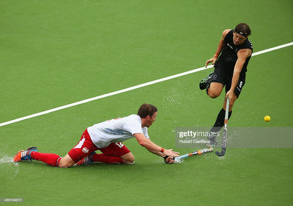 Michael Hoare of England stretches to tackle Blair Hilton of New Zealand in the bronze medal match between New Zealand and England at Glasgow National Hockey Centre during day eleven of the Glasgow 2014 Commonwealth Games on August 3, 2014 in Glasgow, United Kingdom.